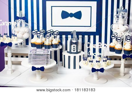 Cake, candies, marshmallows, cakepops, chocolate and other sweets on dessert table at kids birthday party. Birthday Dessert celebration candy bar in white and blue colors.