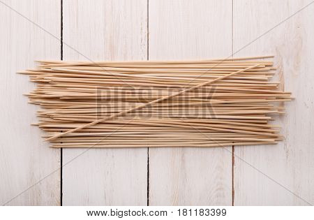 Top view of wooden skewers on white wood surface