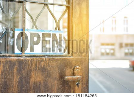 The sign is open on the old vintage doors. A tonal photograph under the antiquity. Concept. A cafe. A restaurant. Dinner. Breakfast. Coffee. Welcome. Retro.