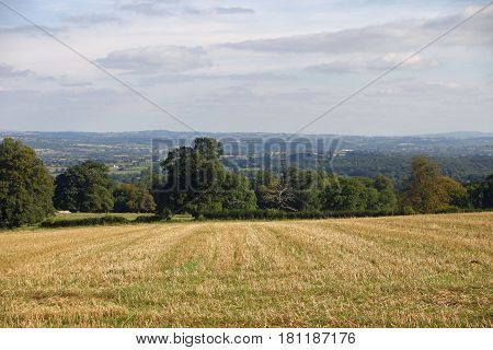 Classical English landscape of rolling hills with fields and trees. Recently cut arable field in the foreground.