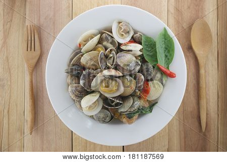 sea clams or RIDGED VENUS CLAM of Stir sauce in white dish on wood background.