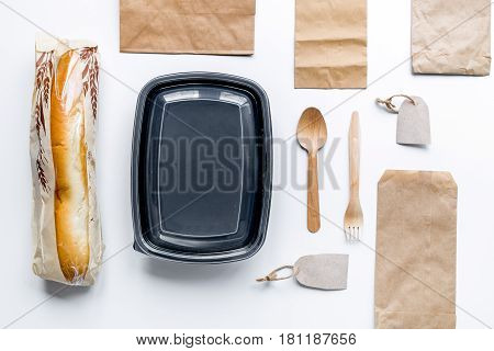 delivery service set with paper bags and sandwich on white desk background top view mock-up