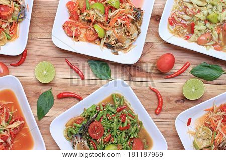 Collection of thai food on wood floorpapaya salad (SOM TUM)Spicy Grilled Pork Salad and Grilled Fish in the food has been popular in Thailand.