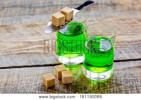 green absinthe with sugar cubes in spoon on wooden table background