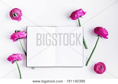 Modern spring design with bright pink flowers and copybook on white desk background top view moke up
