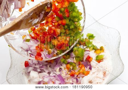 Peruvian ceviche preparation : Add chopped vegetables to the marinated fish