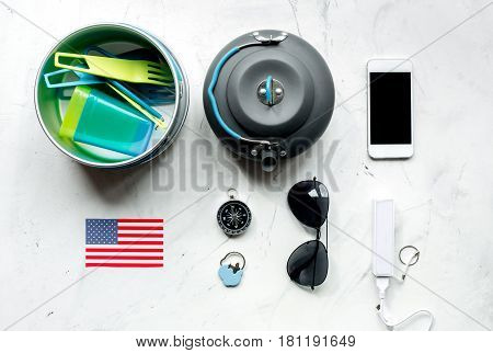 traveller lifestyle items with flags and plactic dishes on white table background top view