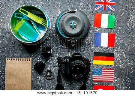 traveller lifestyle items with compass and plactic dishes on gray table background top view