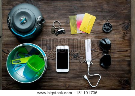 Outfit of traveller with sunglasses and mobile on wooden table background top view
