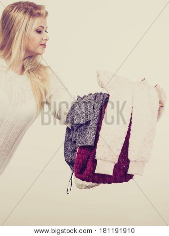 Woman Holding Pile Of Winter Clothes