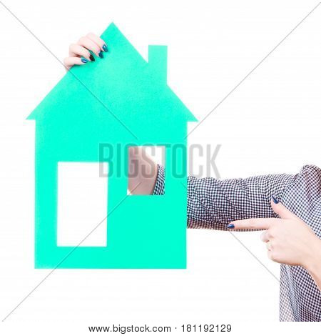 Ownership and property concept. Woman hand holding blue paper house moving to new home.