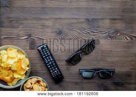 watching movies set with chips and remote control on wooden background top view mock up