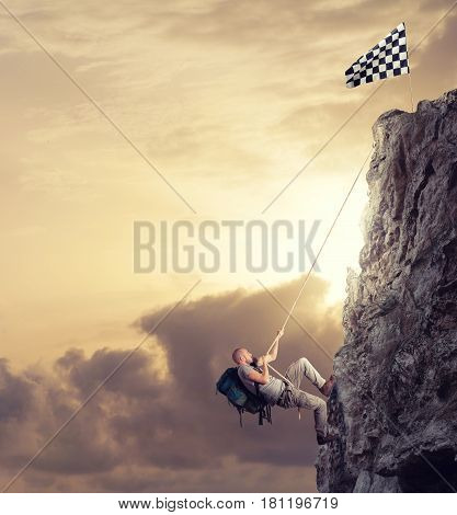 Businessman climb a mountain with a rope to get the flag. Achievement business goal and difficult career concept