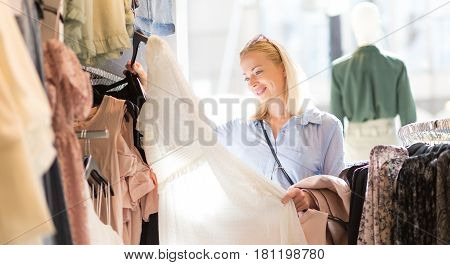 Woman shopping clothes. Female shopper looking at fashionable clothes indoors in clothing store.