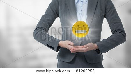 Digital composite of Mid section of business woman with emoji and flare between hands against blurry grey stairs
