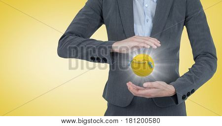 Digital composite of Business woman mid section with emoji between hands and flare against yellow background