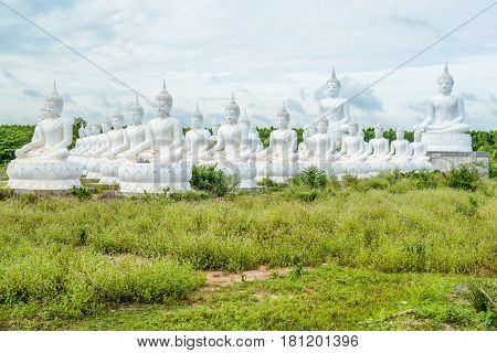 Group of white buddha image in pubic park of thailand