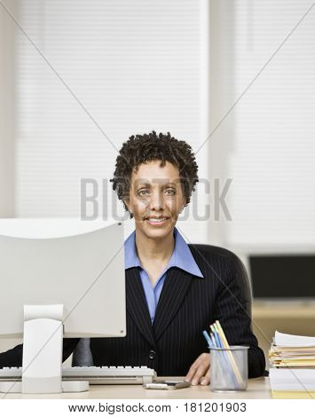 African businesswoman sitting at desk