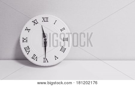Closeup white clock for decorate show half past eleven o'clock or 11:30 a.m. on white wood desk and wallpaper textured background in black and white tone with copy space