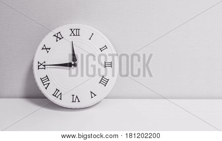 Closeup white clock for decorate show a quarter to twelve o'clock or 11:45 a.m. on white wood desk and wallpaper textured background in black and white tone with copy space