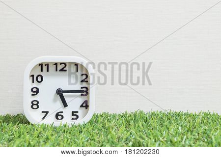 Closeup white clock for decorate show a quarter past five o'clock or 5:15 p.m. on green artificial grass floor and cream wallpaper textured background with copy space