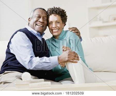 African couple hugging on sofa