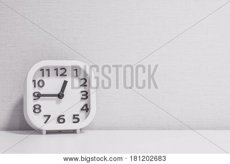 Closeup white clock for decorate show a quarter to one o'clock or 12:45 p.m. on white wood desk and cream wallpaper textured background in black and white tone with copy space