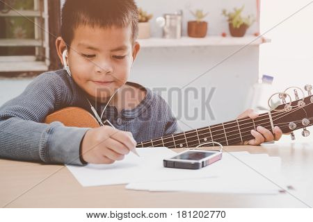 young boy play guitar alone at home