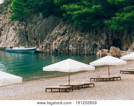Sun beds and umbrellas on the beach. Montenegrin beaches of the Adriatic Sea. Sveti Stefan beach.