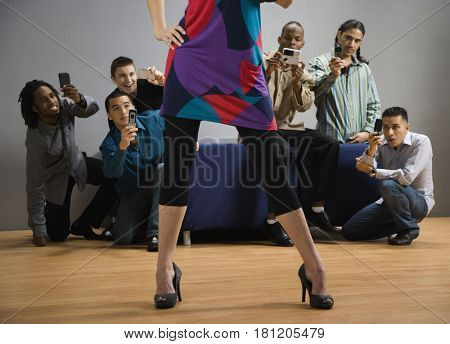 Multi-ethnic men taking photograph of woman