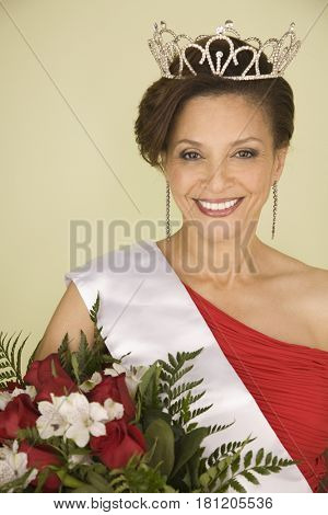 Mixed Race beauty queen holding bouquet of flowers