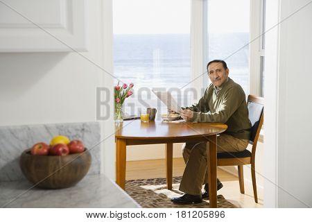 Senior Hispanic man reading newspaper