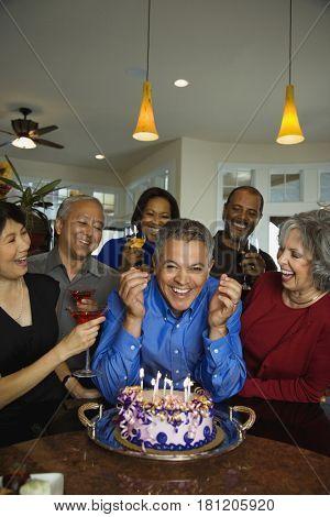 Hispanic man celebrating birthday with multi-ethnic friends