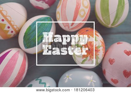 happy easter against painted easter eggs on wooden surface