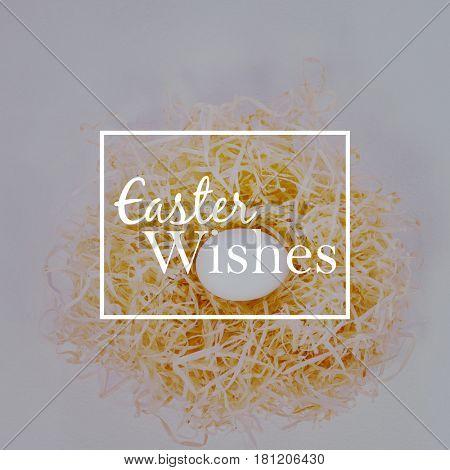 Easter greeting against white easter egg in nest