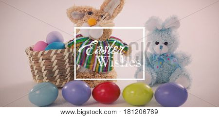 Easter greeting against basket with easter eggs and two toy easter bunny
