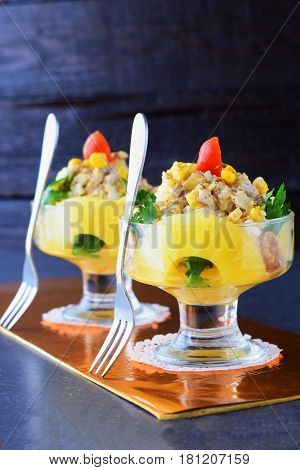 Salad with chiken fillet, pineapple, mushrooms, walnuts in a glass dish on a grey abstract background. Healthy eating concept. Russian traditional food.