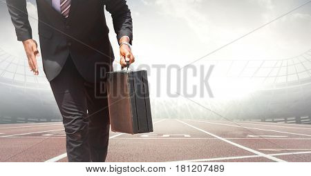 Digital composite of Business man lower body with briefcase at start line on track against flares