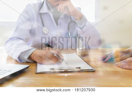 Doctor Explaining Diagnosis To His Female Patient. Physician Giving A Consultation In His Office Dou