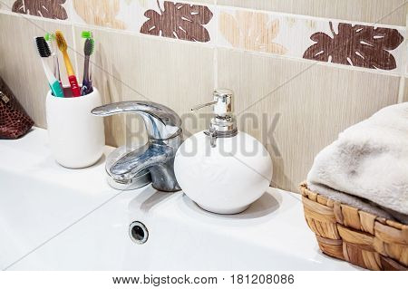 Modern bathroom washbasin with chrome water tap liquid soap and toothbrushes