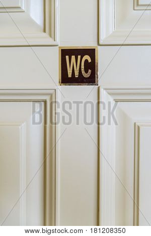 Close up white toilet door with a WC plate on it