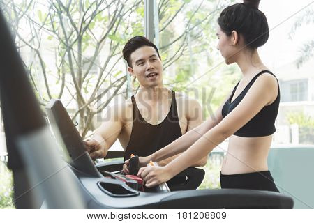 Asian woman in black sportswear with personal trainer on treadmill machine at the gym.