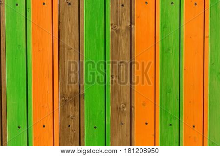 Close up of vertical wooden planks with colourful vertical lines painted on them