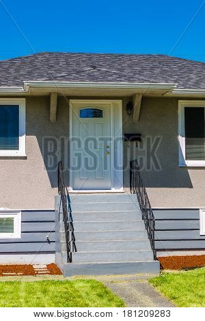 Entrance of modest residential house. Family house with freshly mowed loan on the front yard. Simple residential house in North America with concrete pathway and doorsteps to the entrance