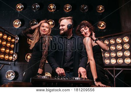 Two adult beautiful girls in nightclub dancing with bearded disk jockey. Music, cool party, famous rhythms, mixed sound.