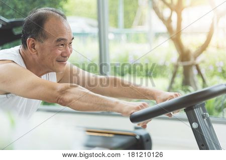 Close up senior man stretching on exercise machine before workout at the gym. copy space.