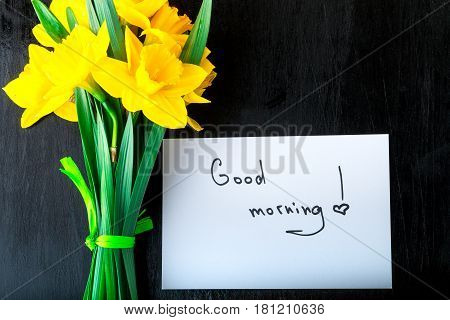 Yellow Daffodil Flowers And Quotes Good Morning On White Rustic Table. Mothers Day Or Womens Day. Gr