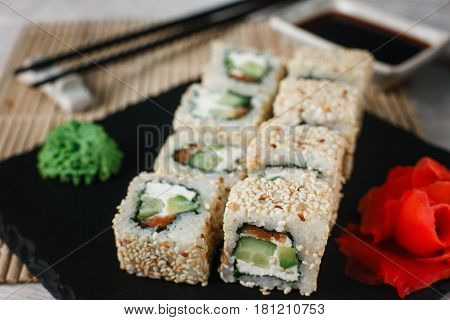 Appetising fresh california sushi roll set with salmon in sesame served on black slate with ginger and wasabi, close up. Japanese healthy seafood.
