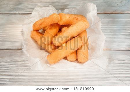 Appetizing fried cheese sticks in paper on white rustic wooden table, closeup. American traditional fast food, national cuisine, beer snack.