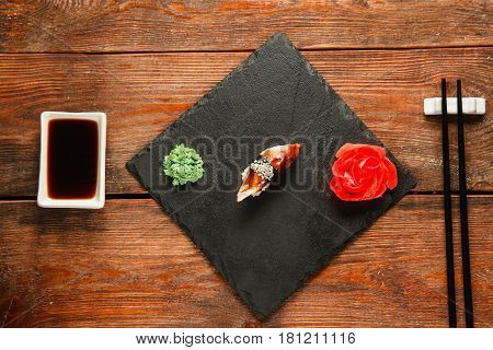Delicious fresh nigiri with smoked eel served on black slate with ginger and wasabi, on wooden rustic table, flat lay. Japanese healthy seafood, traditional cuisine.